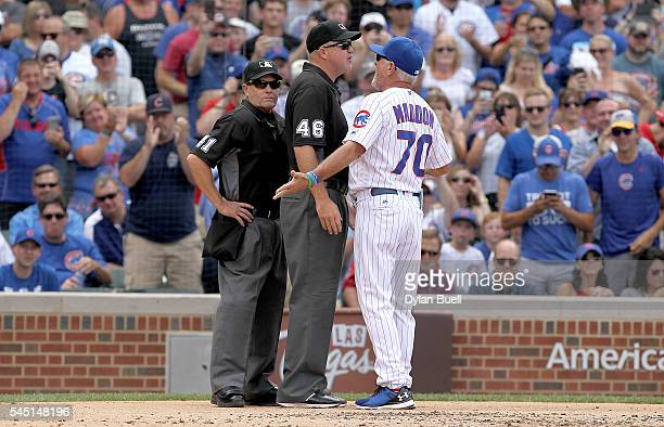 Manager Joe Maddon of the Chicago Cubs argues with umpires Jerry Meals left and Ron Kulpa after being ejected in the second inning against the...