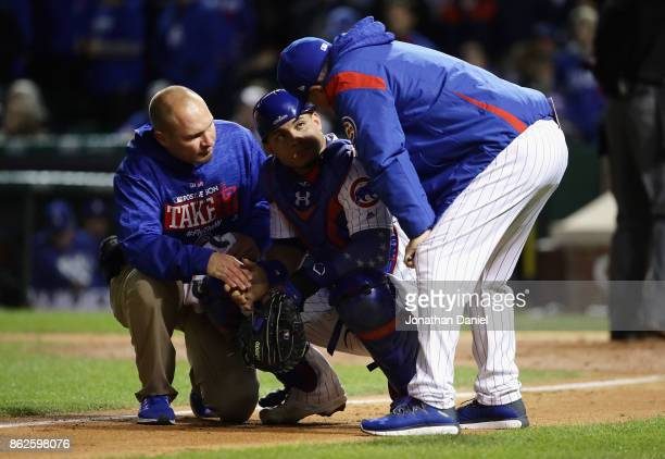 Manager Joe Maddon of the Chicago Cubs checks on Willson Contreras after Contreras was struck by a pitch in the eighth inning against the Los Angeles...