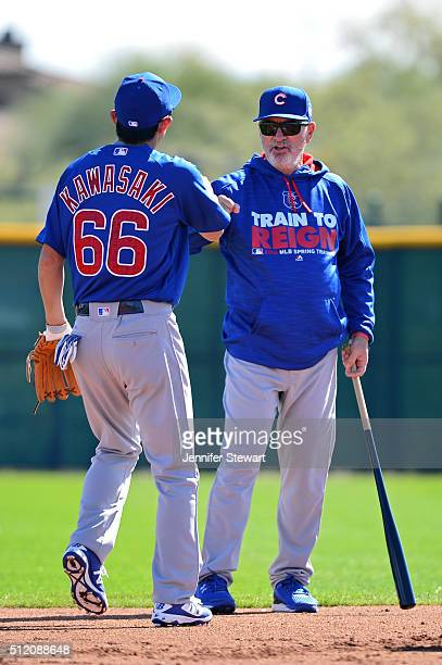 Manager Joe Maddon of the Chicago Cubs fist bumps infielder Munenori Kawasaki during a spring training workout at Surprise Stadium on February 24...