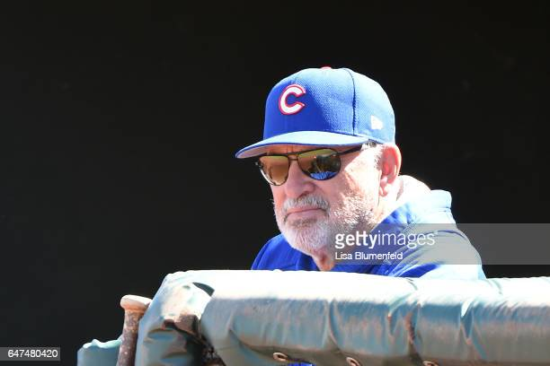 Manager Joe Maddon of the Chicago Cubs looks on from the dugout during the spring training game against the Kansas City Royals at Surprise Stadium on...