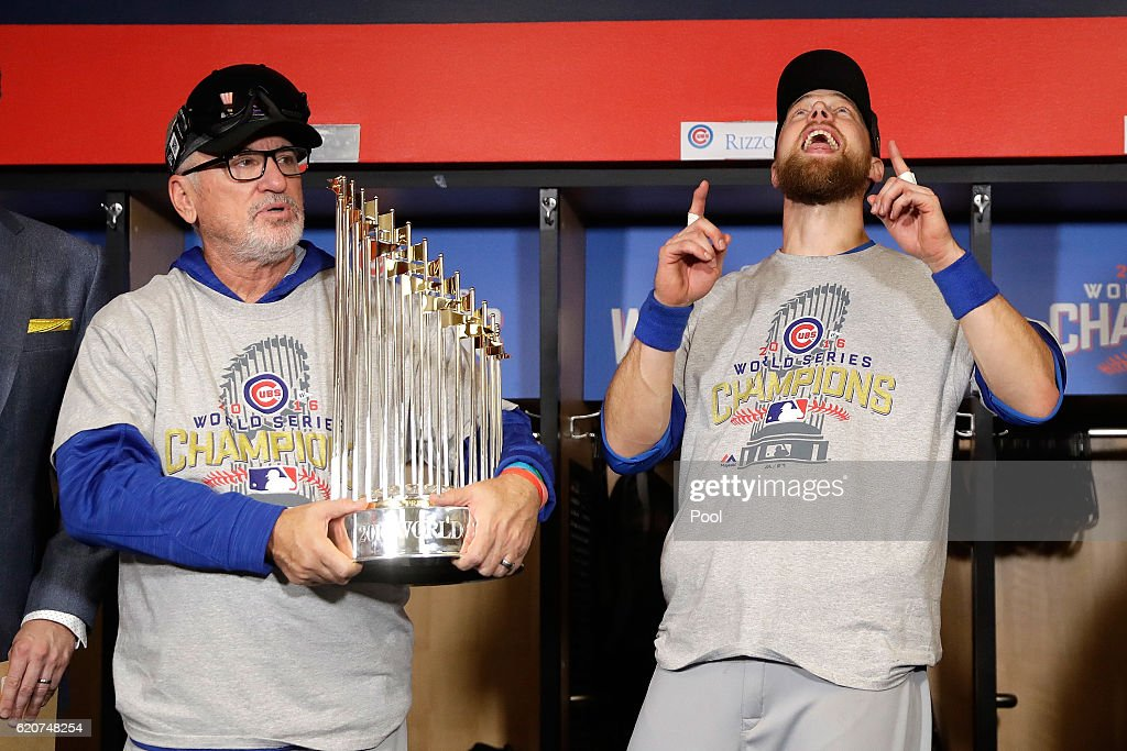 Manager Joe Maddon of the Chicago Cubs poses with The Commissioner's Trophy as Ben Zobrist #18 reacts after the Chicago Cubs defeated the Cleveland Indians 8-7 in Game Seven of the 2016 World Series at Progressive Field on November 2, 2016 in Cleveland, Ohio. The Cubs win their first World Series in 108 years.