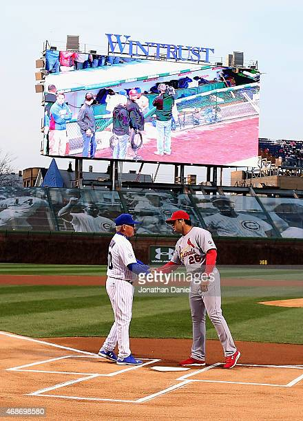 Manager Joe Maddon of the Chicago Cubs shakes hands with manager Mike Matheny of the St Louis Cardinals before the Opening Night game at Wrigley...