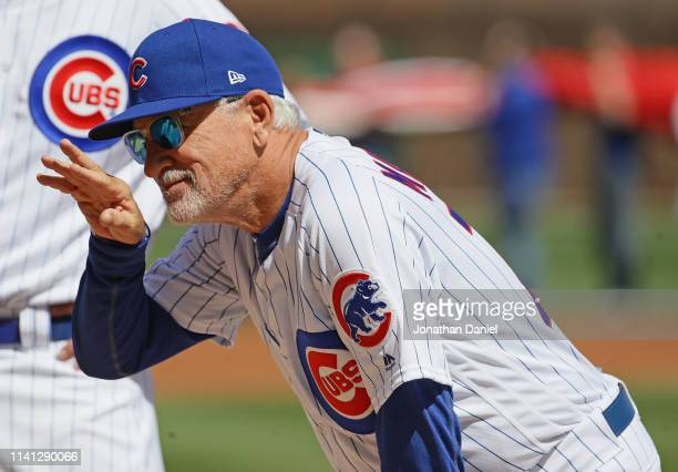 Manager Joe Maddon of the Chicago Cubs waves to a fan during player introductions before the home opening game between the Cubs and the Pittsburgh...