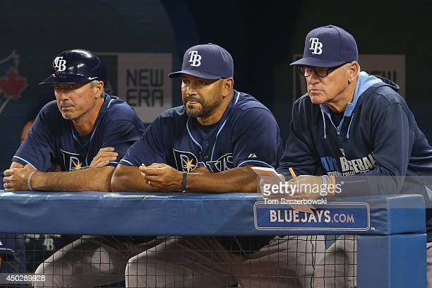 Manager Joe Maddon of the Tampa Bay Rays and bench coach Dave Martinez and third base coach Tom Foley look on from the top step of the dugout during...