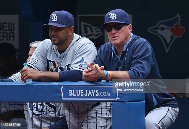 Manager Joe Maddon of the Tampa Bay Rays and bench coach Dave Martinez look on from the top step of the dugout during MLB game action against the...