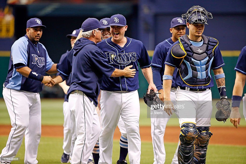Manager Joe Maddon #70 of the Tampa Bay Rays congratulates pitcher Jake McGee #57 after his save against the Minnesota Twins at Tropicana Field on July 11, 2013 in St. Petersburg, Florida.