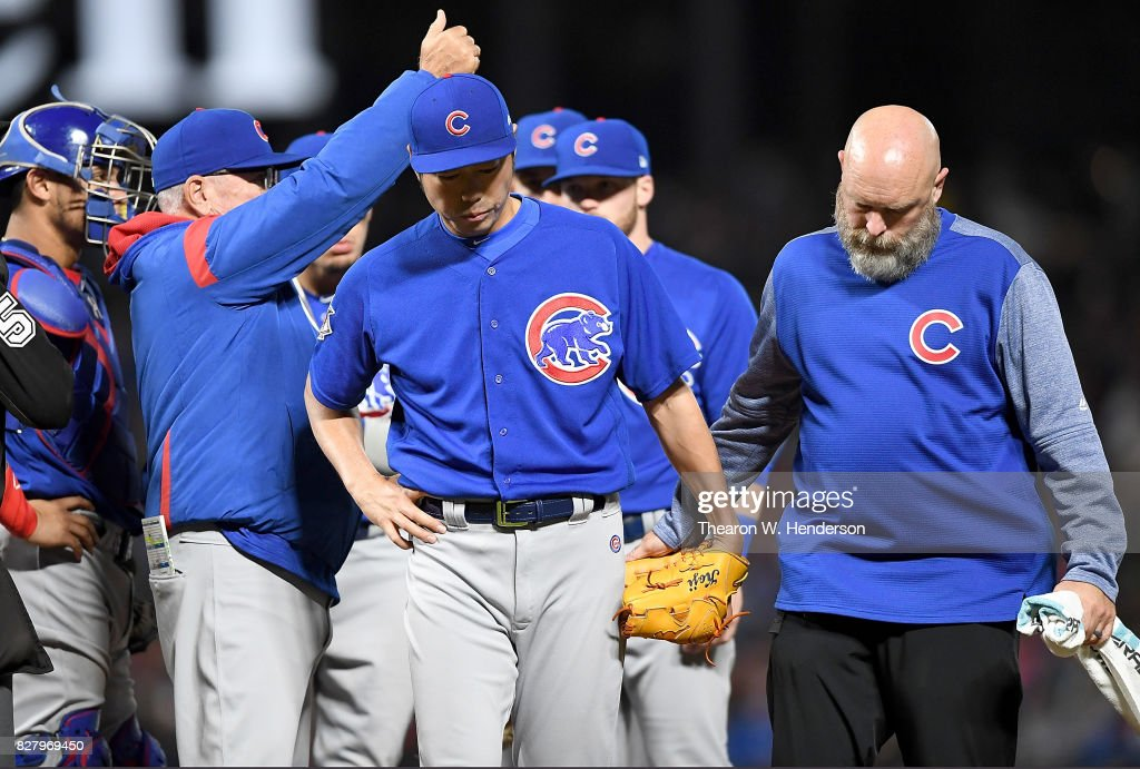 Manager Joe Maddon #70 signals the bullpen to make a pitching change as pitcher Koji Uehara #19 of the Chicago Cubs with an apparent injury is escorted off the field by trainer Ed Halbur during the bottom of the seventh inning against the San Francisco Giants at AT&T Park on August 8, 2017 in San Francisco, California.