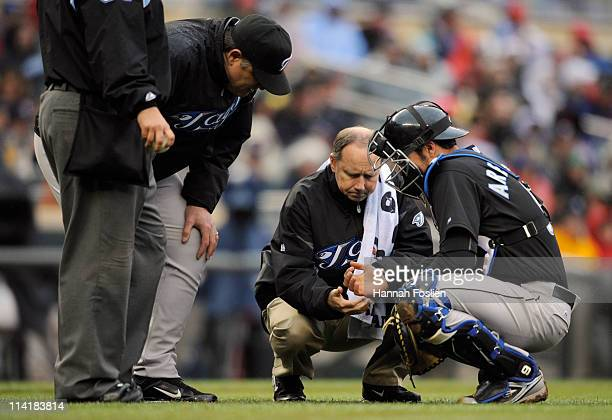 Manager John Farrell and athletic trainer George Poulis of the Toronto Blue Jays check on catcher JP Arencibia of the Toronto Blue Jays during the...