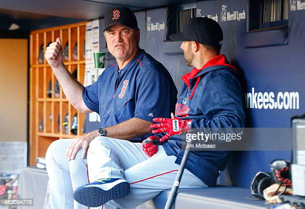 Manager John Farrell and Dustin Pedroia of the Boston Red Sox talk in the dugout before a game against the New York Yankees at Yankee Stadium on...