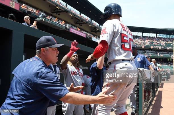 Manager John Farrell of the Boston Red Sox congratulates Mookie Betts after he scored in the first inning against the Baltimore Orioles at Oriole...