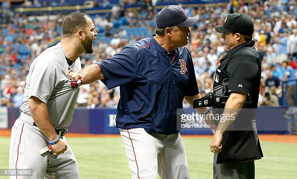 Manager John Farrell of the Boston Red Sox holds back Mike Napoli of the Boston Red Sox as Napoli argues his ejection from the game with umpire Tripp...