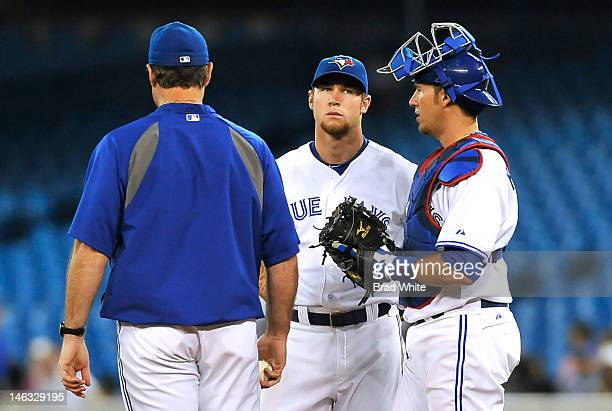 Manager John Farrell of the Toronto Blue Jays talks with Brett Lawrie and JP Arencibia during interleague MLB game action against the Washington...
