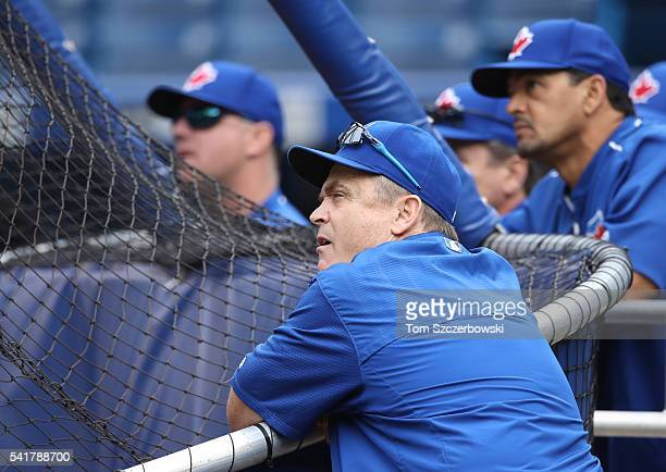 Manager John Gibbons of the Toronto Blue Jays and assistant hitting coach Eric Owens and hitting coach Brook Jacoby and third base coach Luis Rivera...