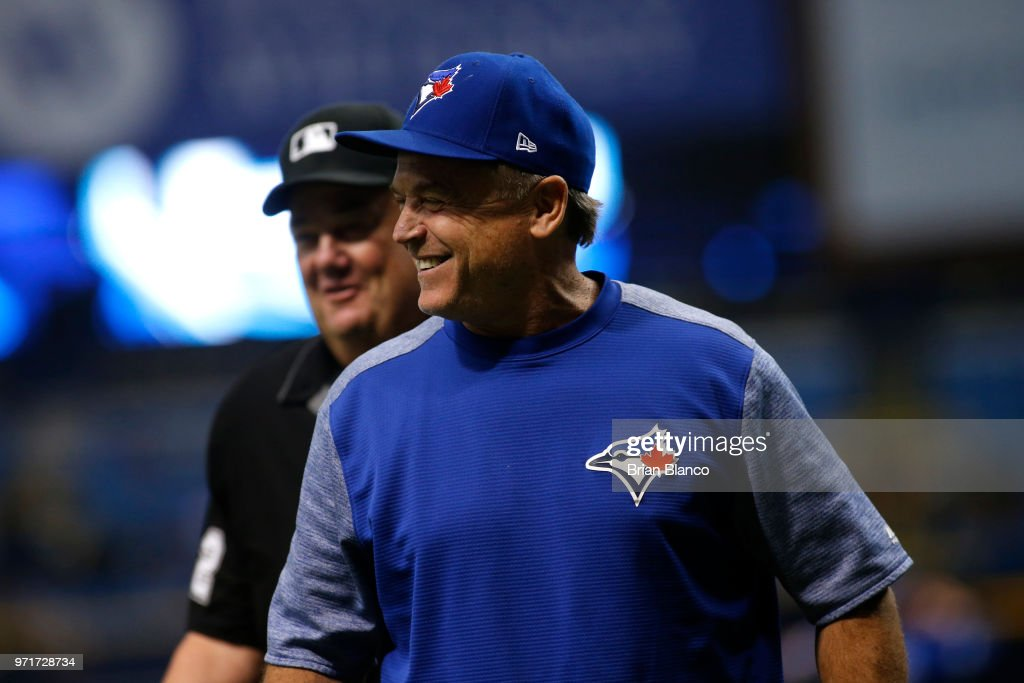 Manager John Gibbons #5 of the Toronto Blue Jays laughs as he walks away from a conversation with umpire Joe West #22 at the start of a game against the Tampa Bay Rays on June 11, 2018 at Tropicana Field in St. Petersburg, Florida.