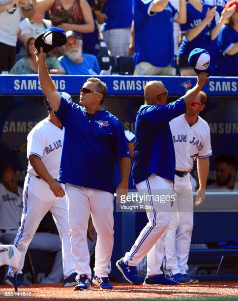 Manager John Gibbons of the Toronto Blue Jays leads his team in waving to the crowd in the fourth inning during MLB game action against the New York...