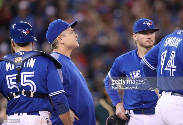 Manager John Gibbons of the Toronto Blue Jays looks on from the mound as he comes out to make a pitching change as Russell Martin and Josh Donaldson...
