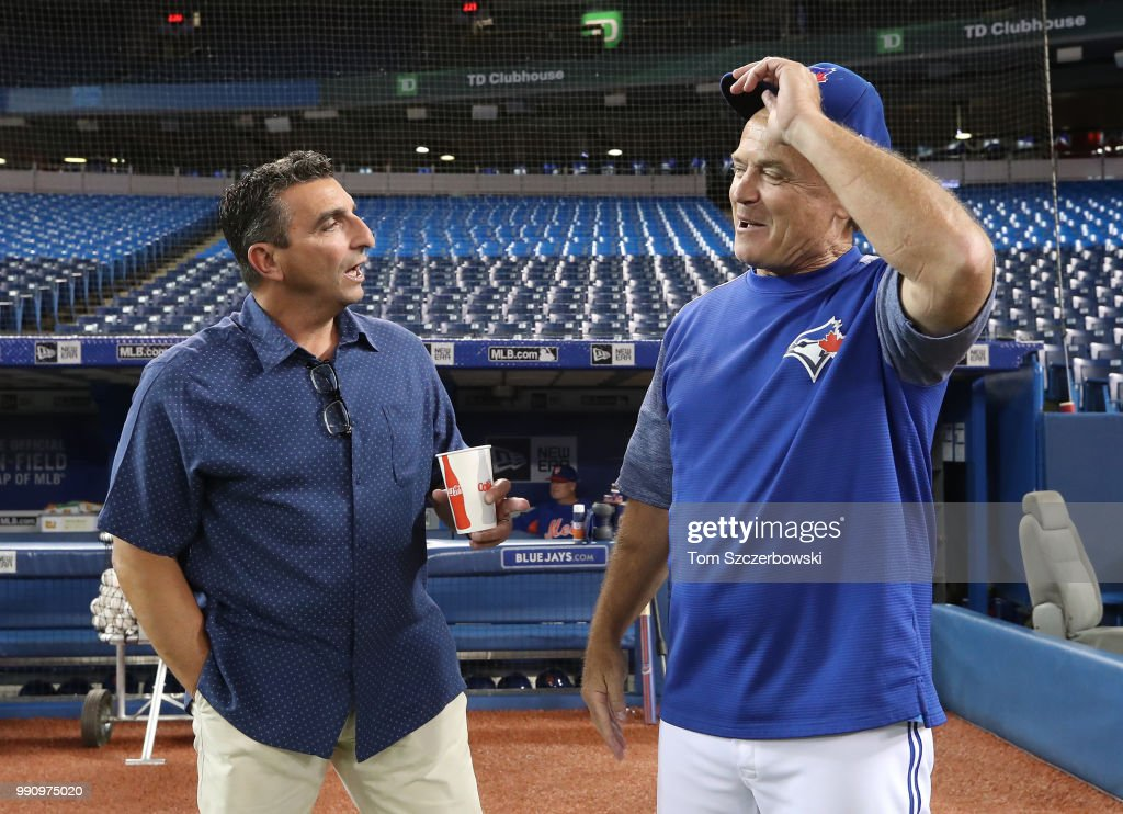 Manager John Gibbons #5 of the Toronto Blue Jays meets with former general manager of the Blue Jays and current special assistant to the New York Mets J.P. Ricciardi before the start of MLB game action against the New York Mets at Rogers Centre on July 3, 2018 in Toronto, Canada.