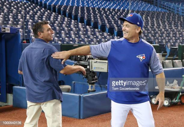 Manager John Gibbons of the Toronto Blue Jays meets with special assistant to the general manager JP Ricciardi of the New York Mets before MLB game...