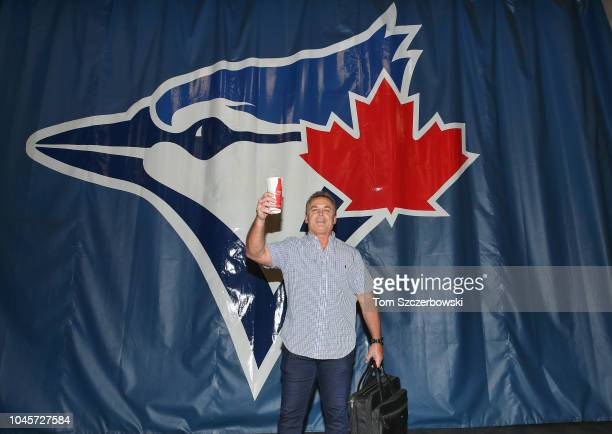 Manager John Gibbons of the Toronto Blue Jays poses by a large curtain with the team logo as he prepares to leave the stadium after their victory and...