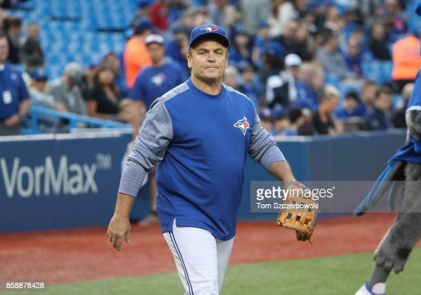 Manager John Gibbons of the Toronto Blue Jays puts on a glove to catch the first pitch from Bob McCown of the Fan 590 radio on the 25th anniversary...