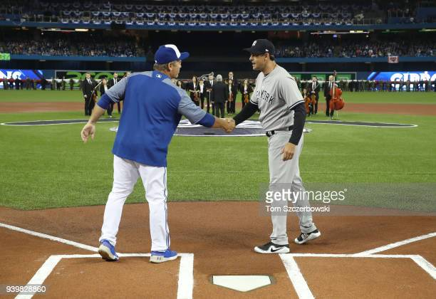 Manager John Gibbons of the Toronto Blue Jays shakes hands with manager Aaron Boone of the New York Yankees on Opening Day during lineup...