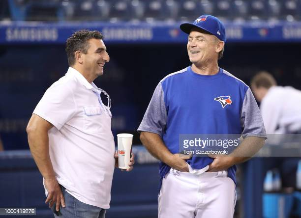 Manager John Gibbons of the Toronto Blue Jays shares a laugh with special assistant to general manager JP Ricciardi as they talk before the start of...