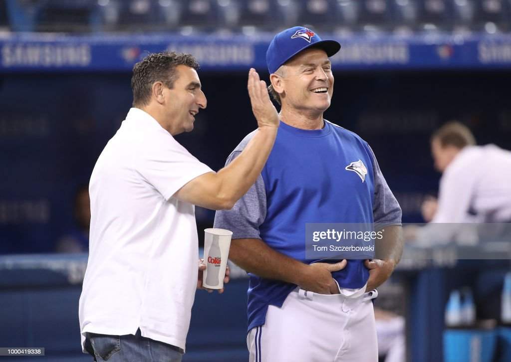 Manager John Gibbons #5 (R) of the Toronto Blue Jays shares a laugh with special assistant to general manager J.P. Ricciardi as they talk before the start of MLB game action against the New York Mets at Rogers Centre on July 4, 2018 in Toronto, Canada.