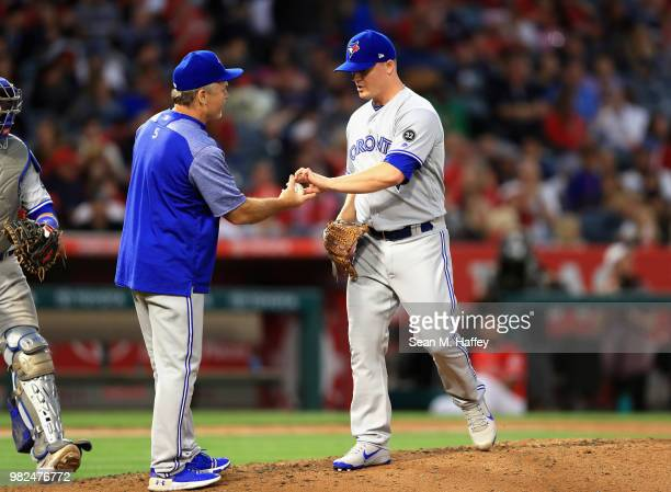 Manager John Gibbons takes out Aaron Loup of the Toronto Blue Jays during the sixth inning of a game against the Los Angeles Angels of Anaheim at...