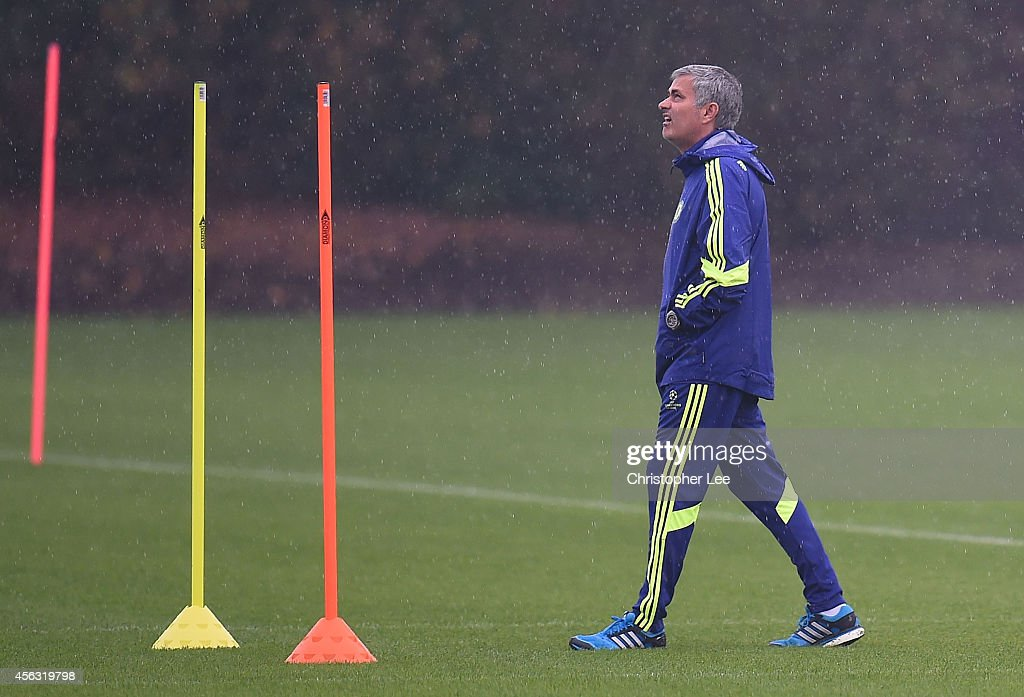 Manager Jose Mourinho looks up to the sky as it rains during the Chelsea Training Session at Chelsea Training Ground on September 29, 2014 in Cobham, England.