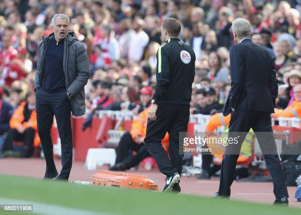 Manager Jose Mourinho of Manchester United and Manager Arsene Wenger of Arsenal speak to the fourth official during the Premier League match between...