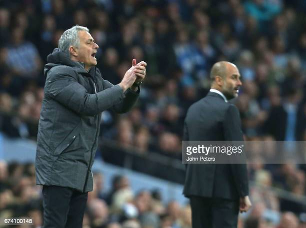 Manager Jose Mourinho of Manchester United and Manager Pep Guardiola of Manchester City watch from the touchline the Premier League match between...