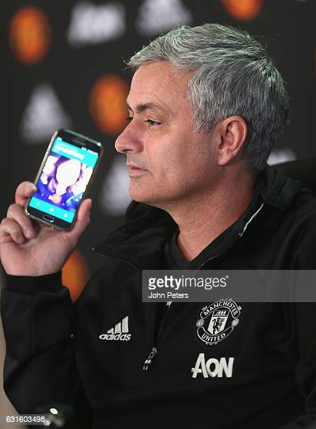 Manager Jose Mourinho of Manchester United answers a journalist's telephone during a press conference at Aon Training Complex on January 13 2017 in...