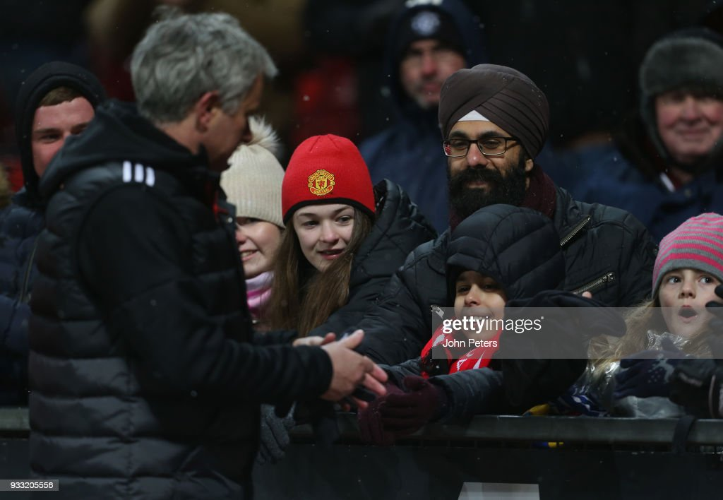 Manager Jose Mourinho of Manchester United gives his hat to a young fan after the Emirates FA Cup Quarter Final match between Manchester United and Brighton & Hove Albion at Old Trafford on March 17, 2018 in Manchester, England.