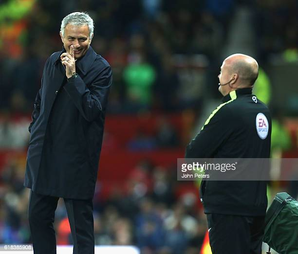 Manager Jose Mourinho of Manchester United shares a joke with fourth official Lee Mason during the EFL Cup Fourth Round match between Manchester...