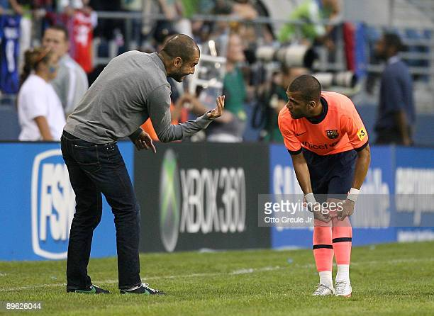 Manager Josep Guardiola of FC Barcelona talks with Daniel Alves during an international friendly match against the Seattle Sounders FC on August 5...