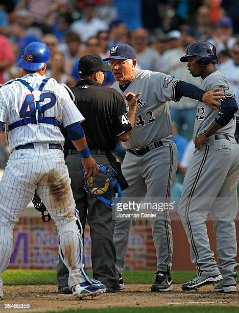 Manager Ken Macha of the Milwaukee Brewers wearing a number 42 jersey in honor of Jackie Robinson holds back player Alcides Escobar as he argues with...