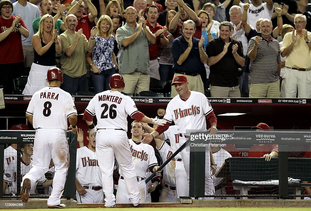 Manager Kirk Gibson (R) and Collin Cowgill #4 (bottom C) of the Arizona Diamondbacks high-five Miguel Montero #26 after he hit a three-run home run against the Colorado Rockies during the fifth inning of the Major League Baseball game at Chase Field on August 30, 2011 in Phoenix, Arizona.