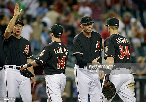 Manager Kirk Gibson of the Arizona Diamondbacks and bench coach Alan Trammell congratulate players Jake Elmore and Mike Jacobs following their 82...