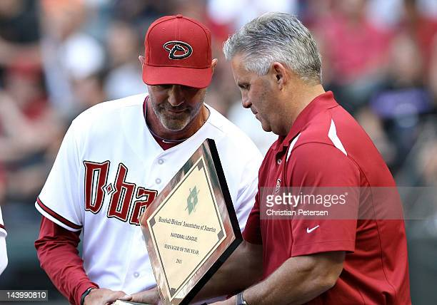 Manager Kirk Gibson of the Arizona Diamondbacks receives the NL Manager of the Year Award from GM Kevin Towers before the Opening Day game against...