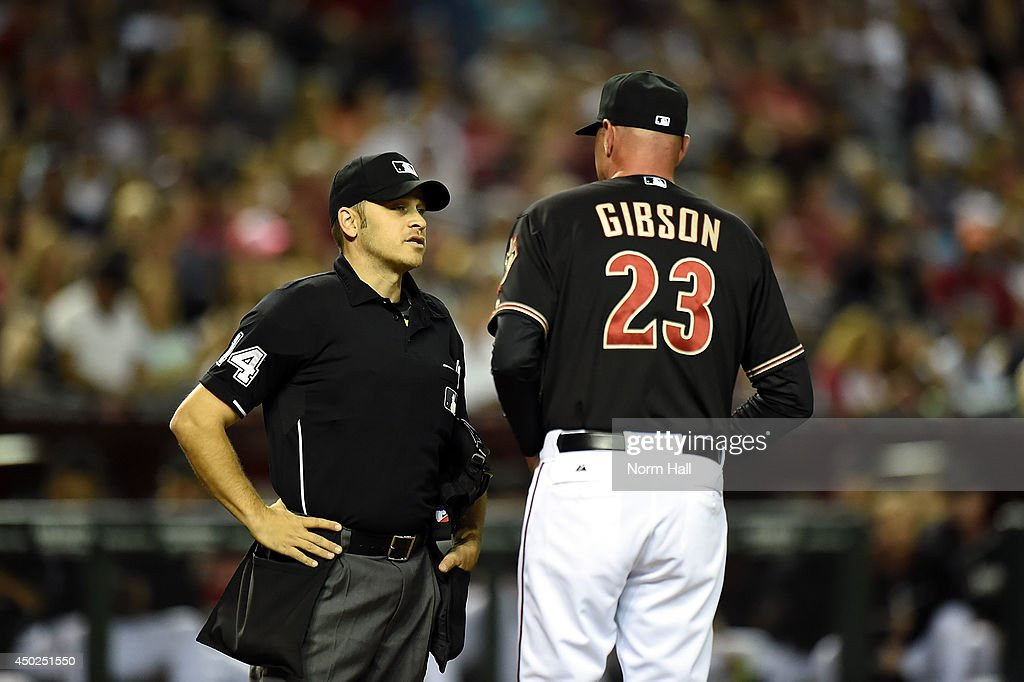 Manager Kirk Gibson #23 of the Arizona Diamondbacks talks with home plate umpire Mark Wegner #14 during the third inning of a game against the Atlanta Braves at Chase Field on June 7, 2014 in Phoenix, Arizona.