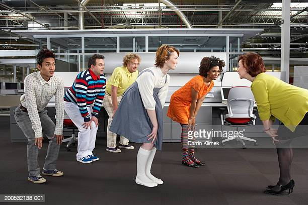 manager leading workers in game, workers in childlike clothing - bending over in skirt stock pictures, royalty-free photos & images