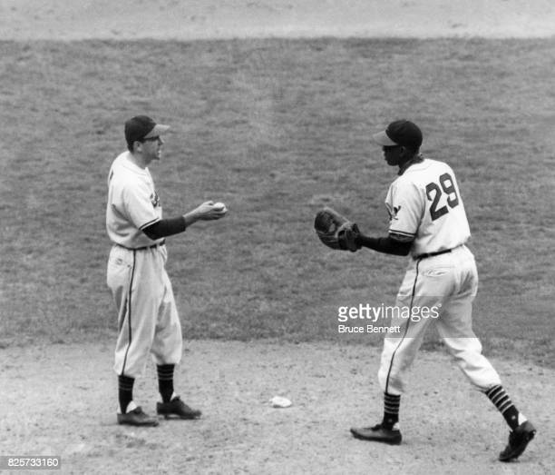 Manager Lou Boudreau of the Cleveland Indians hands the ball to relief pitcher Satchel Paige during Game 5 of the 1948 World Series against the...