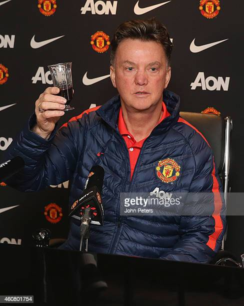 Manager Louis van Gaal of Manchester United shares a drink of red wine with journalists during a press conference at Aon Training Complex on December...
