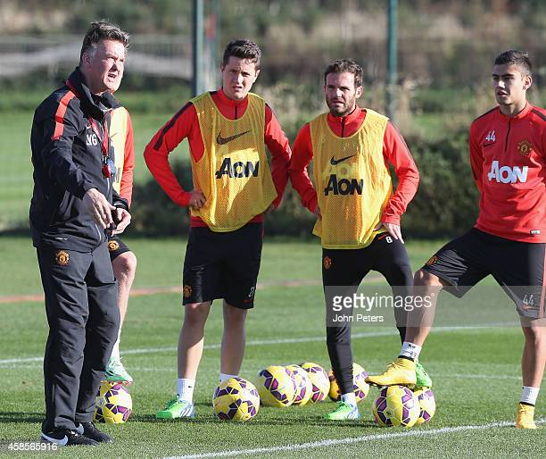 Manager Louis van Gaal of Manchester United speaks to Ander Herrera, Juan Mata and Andreas Pereira during a first team training session at Aon...