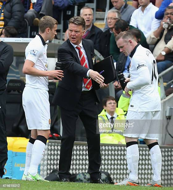 Manager Louis van Gaal of Manchester United speaks to James Wilson and Wayne Rooney during the Barclays Premier League match between Hull City and...