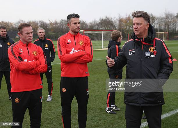 Manager Louis van Gaal speaks to Wayne Rooney and Robin van Persie of Manchester United during a first team training session at Aon Training Complex...