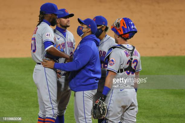 Manager Luis Rojas of the New York Mets talks with pitcher Miguel Castro as J.D. Davis, Francisco Lindor and James McCann listen during a game...