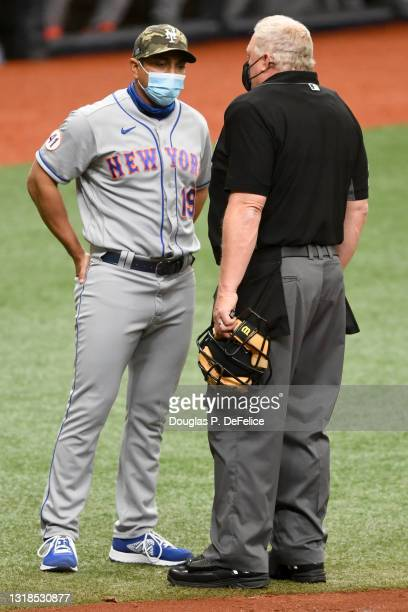 Manager Luis Rojas of the New York Mets talks with umpire Bill Miller at the end of the third inning against the Tampa Bay Rays at Tropicana Field on...