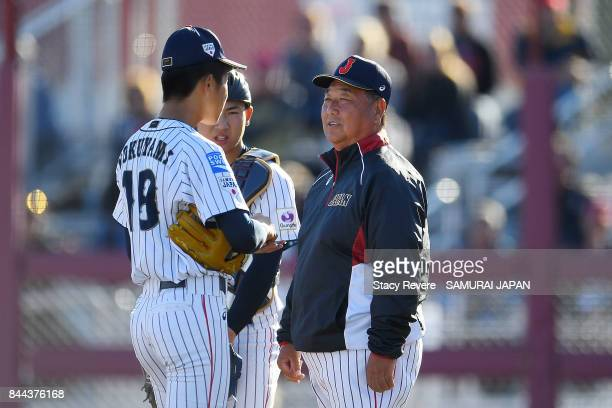 Manager Mamuro Koeda of Japan speaks with Shoma Tokuyama during the third inning of a game against Canada during the WBSC U18 Baseball World Cup...