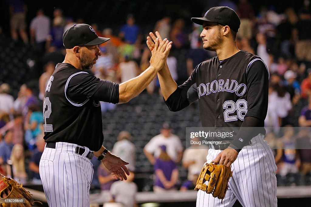 Manager manager Walt Weiss #22 and Nolan Arenado #28 of the Colorado Rockies celebrate their 10-5 victory over the Arizona Diamondbacks at Coors Field on June 23, 2015 in Denver, Colorado.